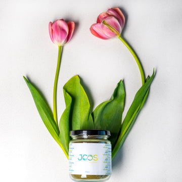 JOOS brain power blend 90 gram glass jar against two pink tulips.