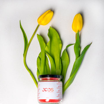 JOOS Immune Boost blend 90 gram glass jar against two yellow tulips.