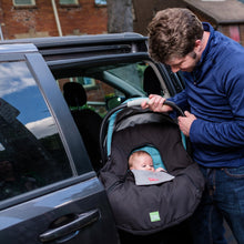 baby parka black car seat cover on seat ready to go in vehicle held by proud dad