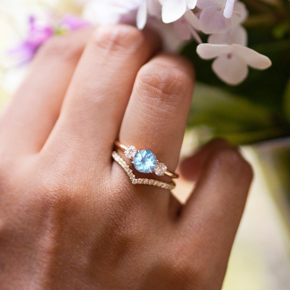 Round Cut Aquamarine Trilogy Engagement Ring and Chevron Band from Fenton on a hand