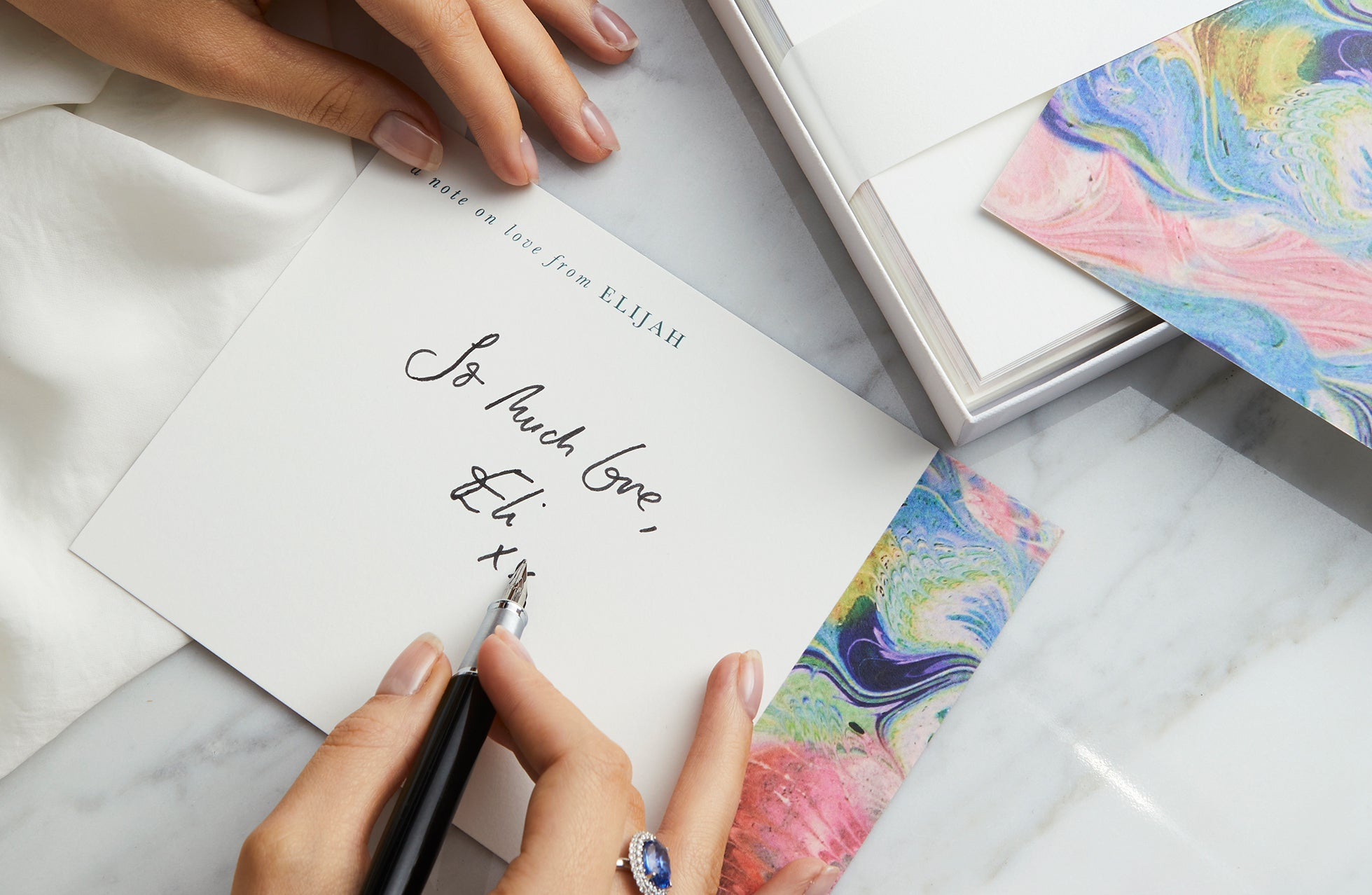 Women wearing a blue sapphire ring and writing a note card on stationary from Fenton x Papier.
