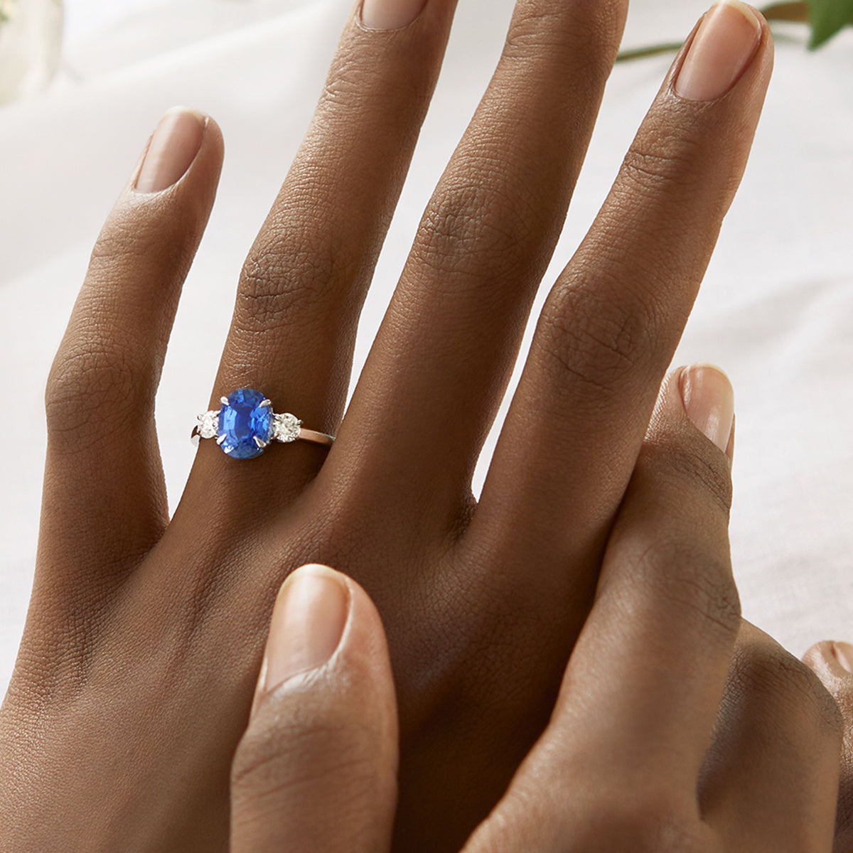 Clean Oval Cut Blue Sapphire Trilogy Ring from Fenton on a hand