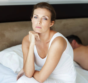 Woman sitting up in bed staring off contemplatively.