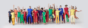 Group of people wearing brightly colored t-shirts jumping excitedly.