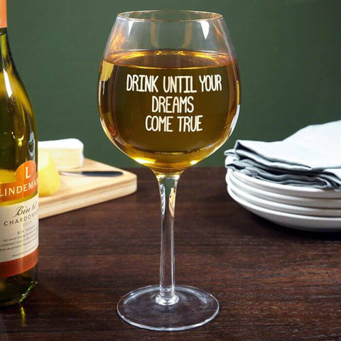 statement wine glass with text that reads drink until your dreams come true