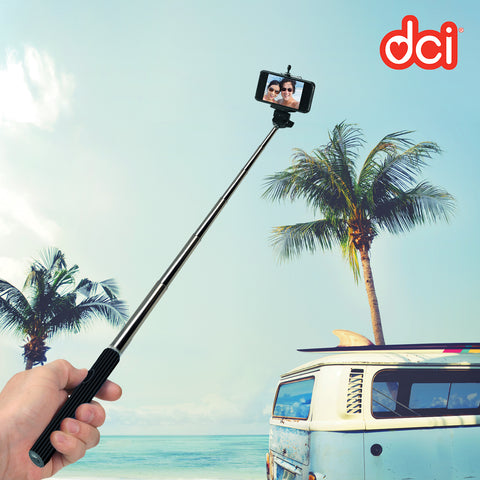 a phone with image of two girls  attached bluetooth selfie stick with beach background and a camper van