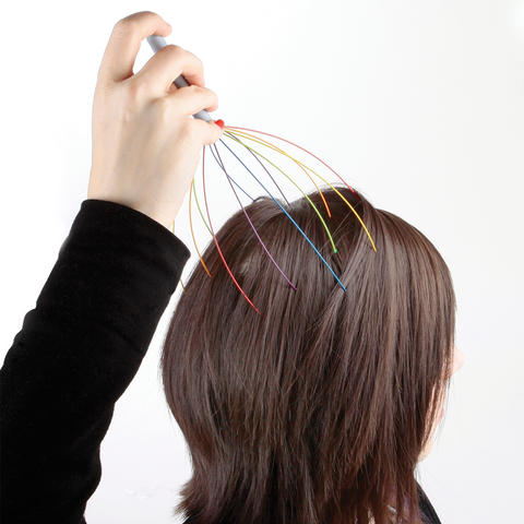 a woman massaging her head using rainbow head massager