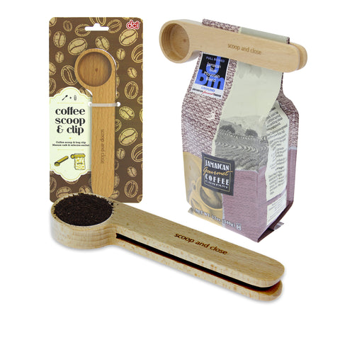 scoop with coffee lying down with packaging and a pack of coffee clipped by the coffe scoop and clip