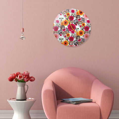 cat wall clock hanging on pink wall in living room with pink sofa chair, table with flower vase and light bulb