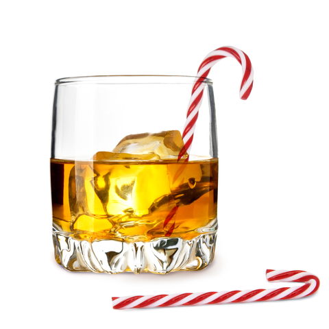 a half filled glass of whiskey with ice cubes and a candy cane drink stirrer