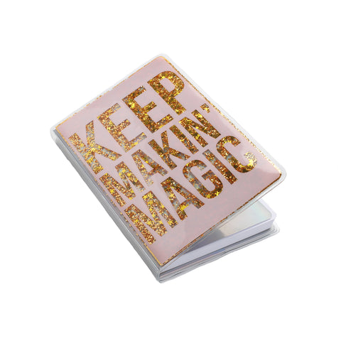 slightly opened pink journal in a vinyl cover with text keep makin' magic with gold floating glitter in each letter