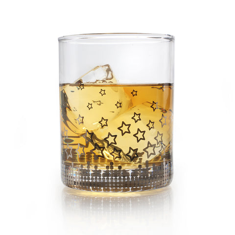a highball glass with silver stars pattern filled with whiskey and ice
