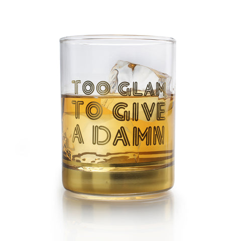 a highball glass with text too glam to give a damn filled with whiskey and ice