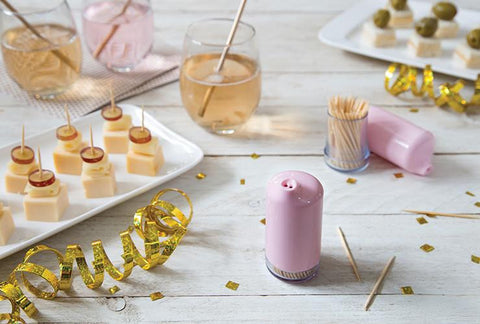 a table set up with confetti, glass filled with juice, desserts and close pigtooth toothpick dispenser and open pigtooth toothpick dispenser