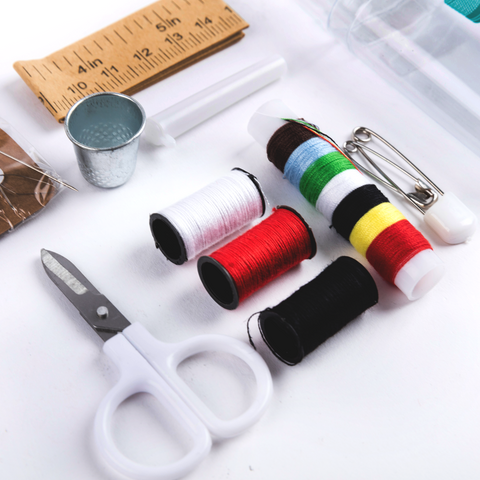 pair of scissor, white thread, red thread, black thread, assorted colors thread, pin, thimbles, measuring tape, needle