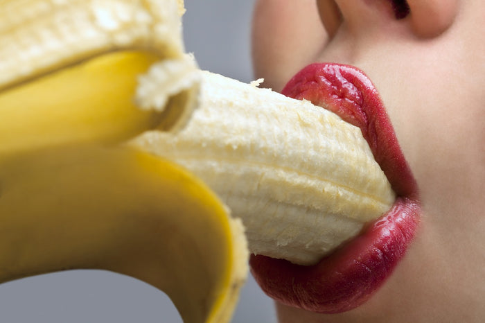 woman with banana in mouth
