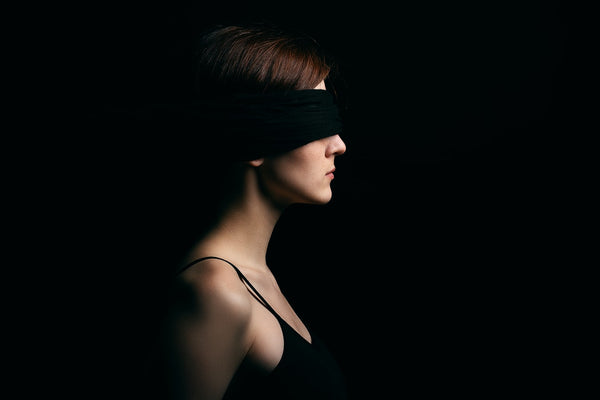 Woman blindfolded - blindfolding and sound isolation headphones are examples of sensory deprivation