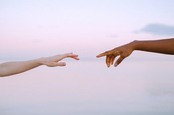two hands reaching toward each other