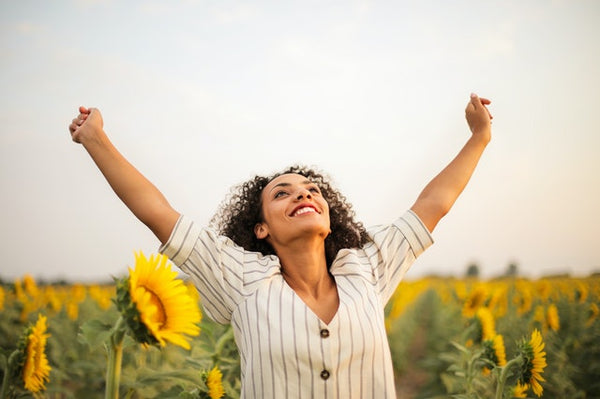 woman in sunflower field with hands in air