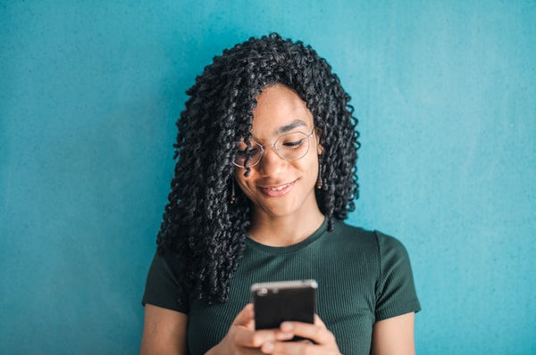 person of color texting in front of blue wall