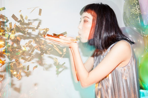 Woman blowing gold confetti out of her hands
