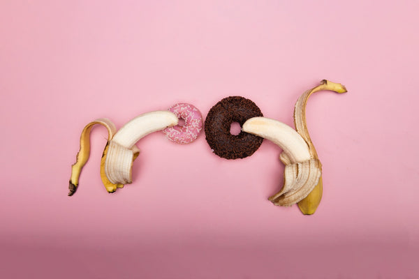 two bananas next to two donuts