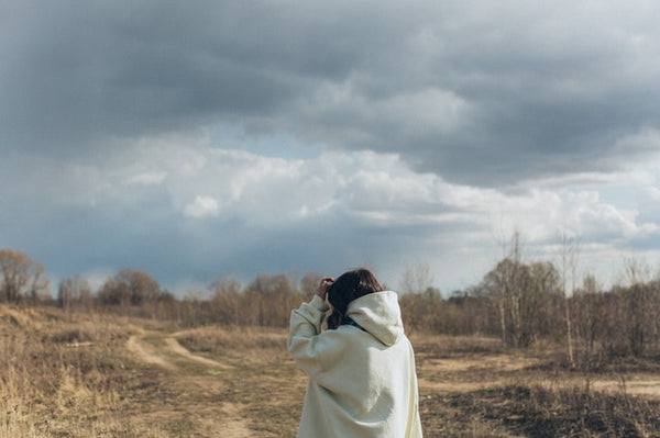 woman looking out into cloudy sky and field
