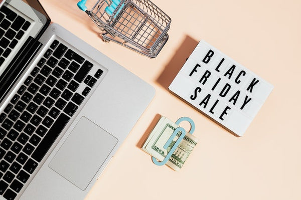 laptop and money next to black friday text