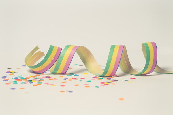 Confetti and rainbow ribbon laying on a cream background