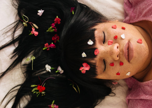 Sensual young lady with flowers in her hair meditating - orgasms and stress relief