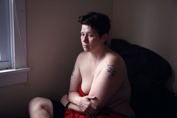 man sitting topless in bed