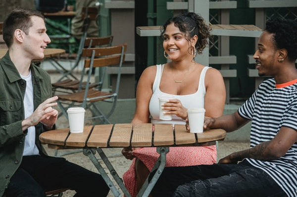 three people talking outside with coffee cups