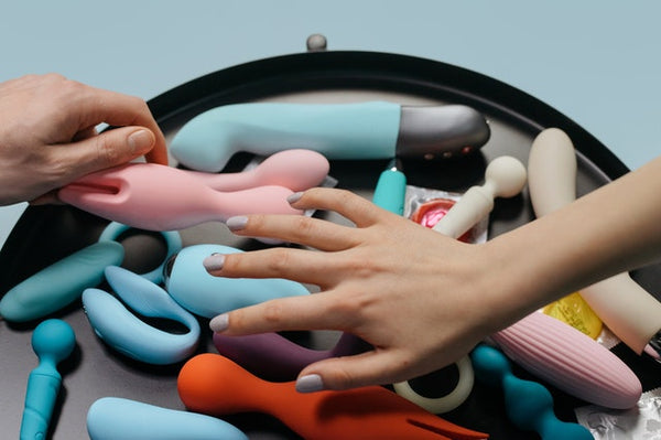 hands picking vibrators from pile