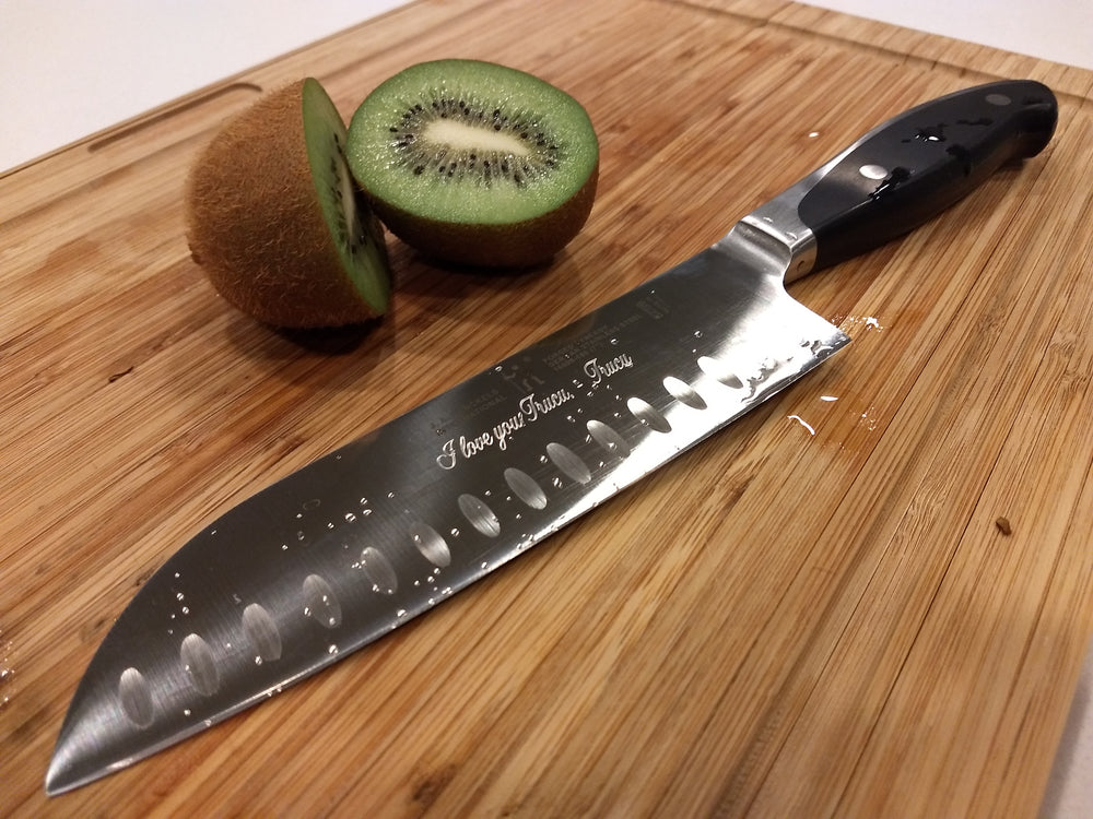 Engraved Chefs Knife on a cutting board with a sliced kiwi