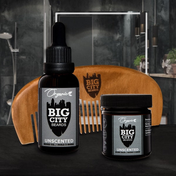 This photo is set in a modern bathroom setting. It has a dark grey slate tile shower in the background and features a large bottle of organic beard oil unscented and a large organic beard balm unscented sitting infront of a natural wood beard comb