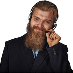A friendly bearded customer service representative smiling and ready to assist with any questions while wearing a headset.