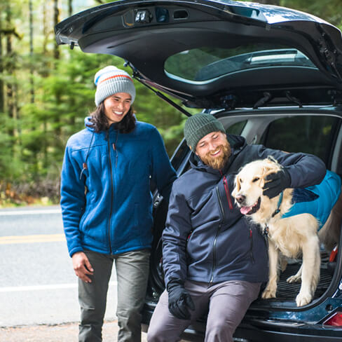 Couple and a dog sitting on the back of an SUV