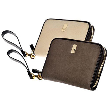 The Güs Clutch is a combined purse and wallet for women looking for something special and not wanting to carry too much. It's a sexy piece with a detachable leather wrist strap. Available in Latte and Mocha Pony Hair suede with 24K gold trim. Both colors shown.