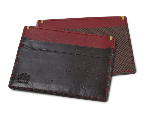 The Güs Card Case featuring the Spitshot perforation in brown and black saddle leather with Chili Pepper calfskin lining.
