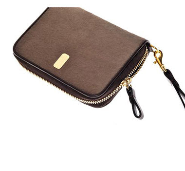 The Güs Clutch is a combined purse and wallet for women looking for something special and not wanting to carry too much. It's a sexy piece with a detachable leather wrist strap. Available in Latte and Mocha Pony Hair suede with 24K gold trim. Top view.