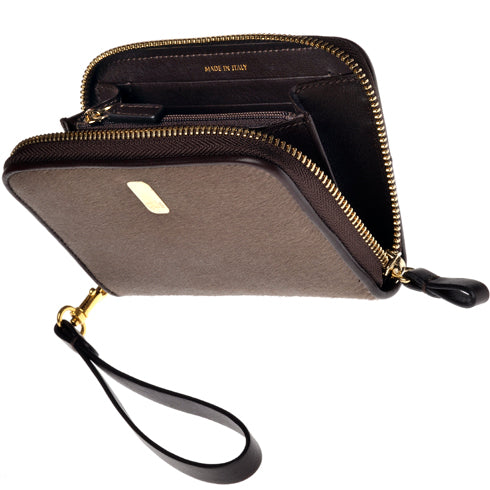 The Güs Clutch is a combined purse and wallet for women looking for something special and not wanting to carry too much. It's a sexy piece with a detachable leather wrist strap. Available in Latte and Mocha Pony Hair suede with 24K gold trim. Front view open.