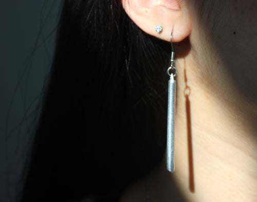 Hanging bar earrings made from bombs dropped in Laos