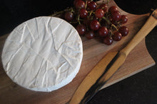 wooden knife with brie wheel and red grapes on cutting board