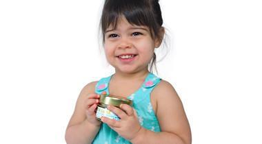 young smiling girl holding shea butter baby balm