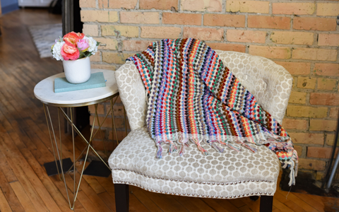 The Rainbow Pattern Towel-blanket on a chair