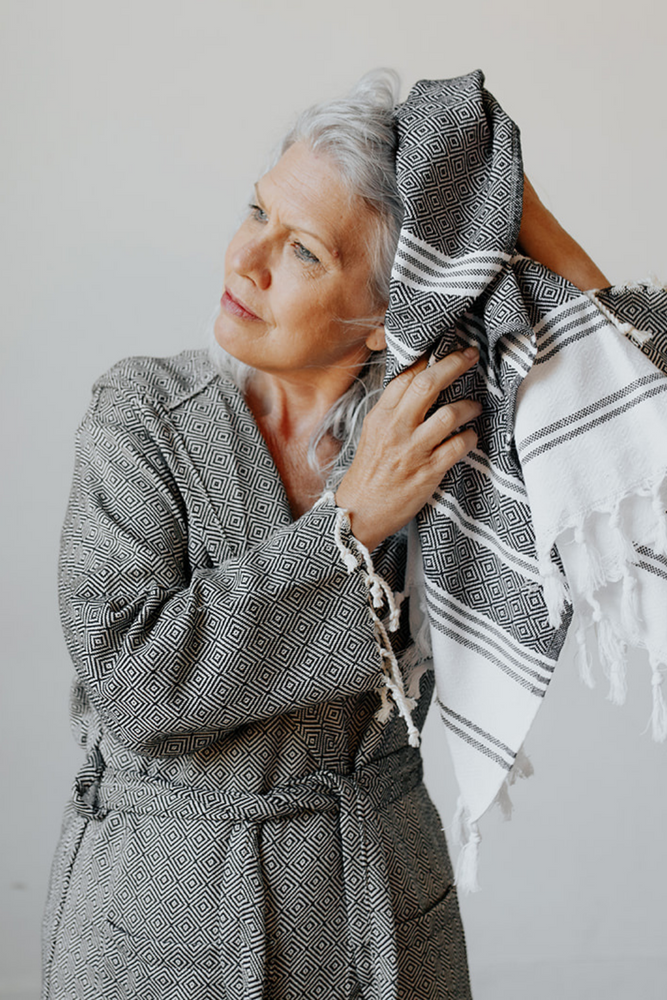 Woman drying her hair with the Diamond Stripe Hand Towel in Charcoal