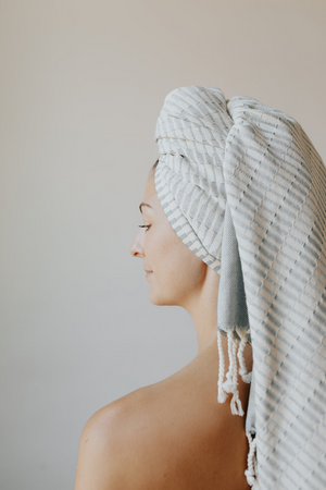 Load image into Gallery viewer, Woman using the Raised Weave Turkish Towel in Teal as a head wrap