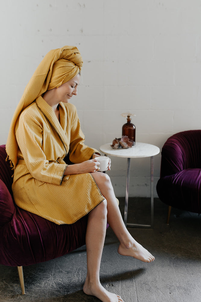 Woman wearing the Waffle Weave Bathrobe in Mustard and the matching towel as a head wrap