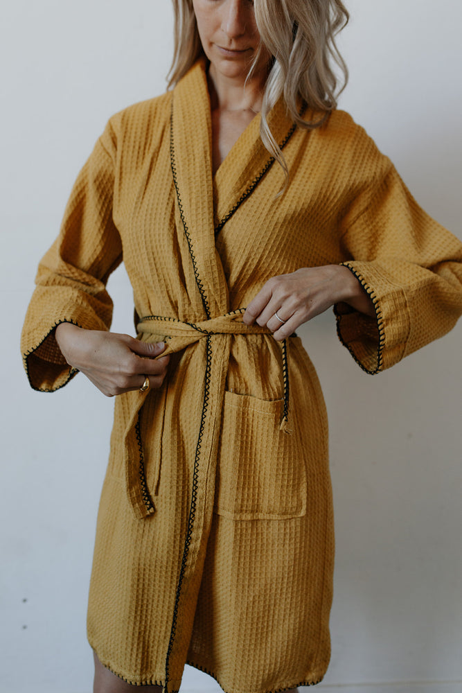 Load image into Gallery viewer, Woman tying her Waffle Weave Bathrobe in Mustard