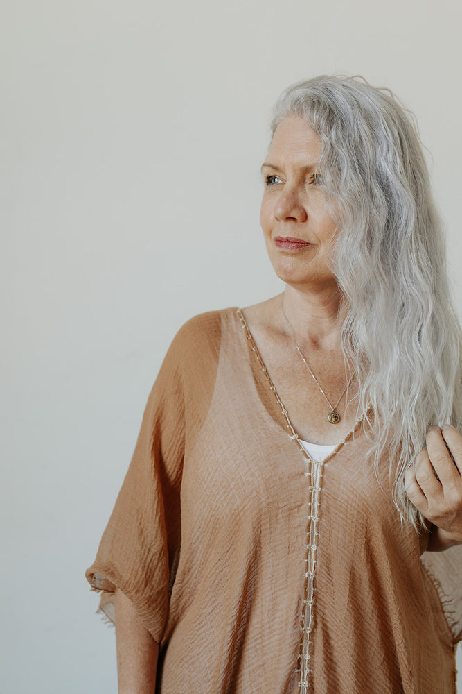 Woman wearing the Byzantine Coin Necklace and KISA loungewear